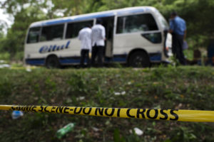 Forensic teams working at a crime scene where two people were killed on a public transport unit in the town of Choloma, Honduras.