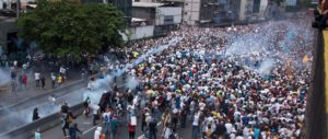 Demonstrators clash with riot police during a march against Venezuelan President Nicolas Maduro, in Caracas on April 19, 2017.