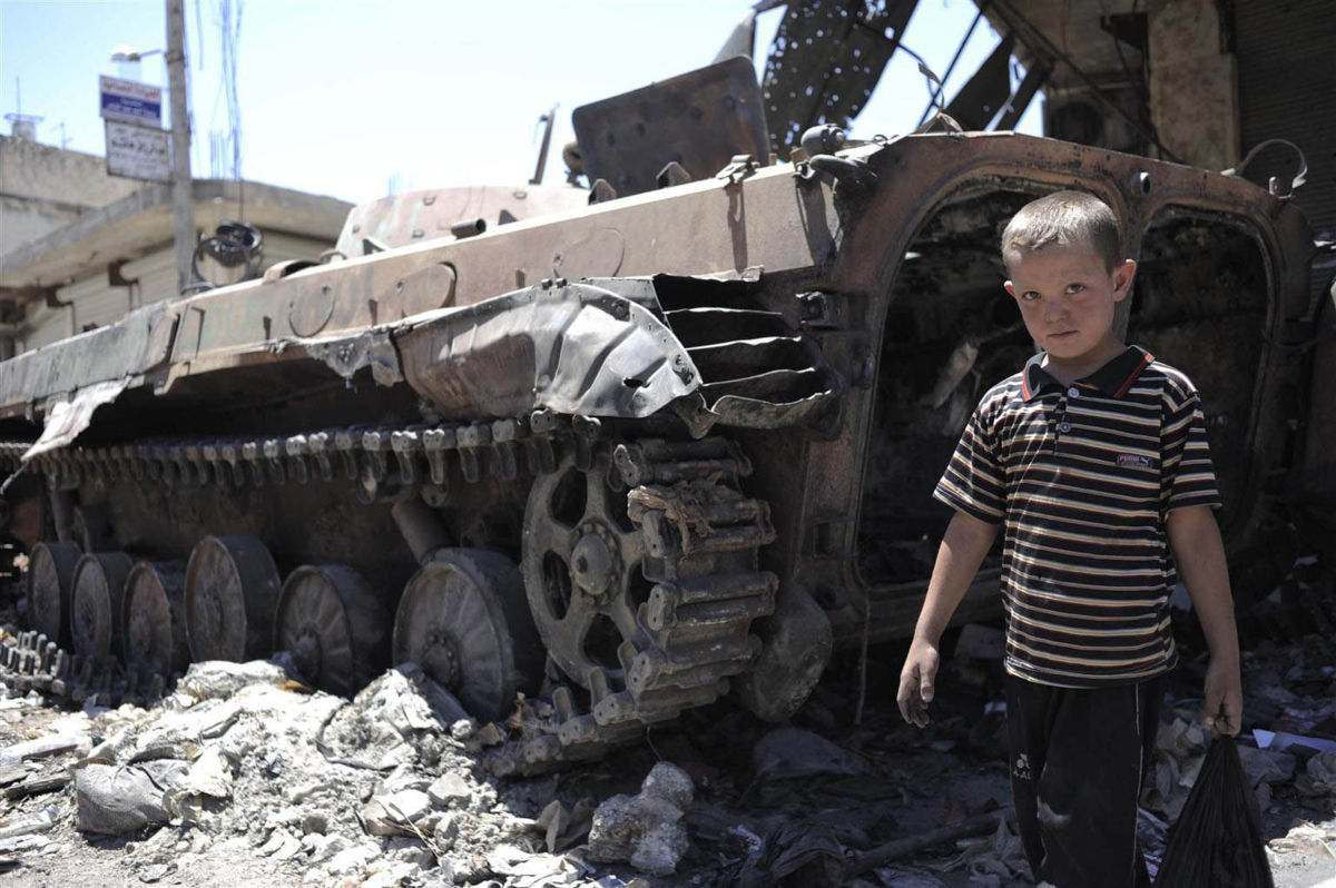 [THIS IMAGE IS FOR USE BY UNICEF ONLY  DO NOT SHARE WITH EXTERNAL MEDIA] On 3 July, a boy walks by a destroyed armoured personnel carrier, surrounded by rubble, in a town affected by the conflict.  By July 2012 in Syria, escalating conflict between rebel and government forces is taking an increasing toll on children and their families. Deaths, including of children and women, have surpassed 17,000, and an estimated 1.5 million people inside Syria are in need of humanitarian assistance. Education and health services have been disrupted, and food insecurity is rising. Up to 1 million people have been internally displaced, with an increasing number being displaced for a second time as the conflict continues to spread. Over 120,000 refugees  half of them children  have fled to neighbouring Iraq, Jordan, Lebanon and Turkey. UNICEF is working with diverse governments, the United Nations High Commission for Refugees (UNHCR) and local and international NGOs to respond to the needs of affected children, both in and outside the country. UNICEF supports initiatives in education, water, sanitation and hygiene and child protection, including psychosocial assistance for children traumatized by the conflict to which they have been subjected or borne witness. UNICEF has requested US$39.2 million to fund this work, of which only 30 per cent has been received to date.